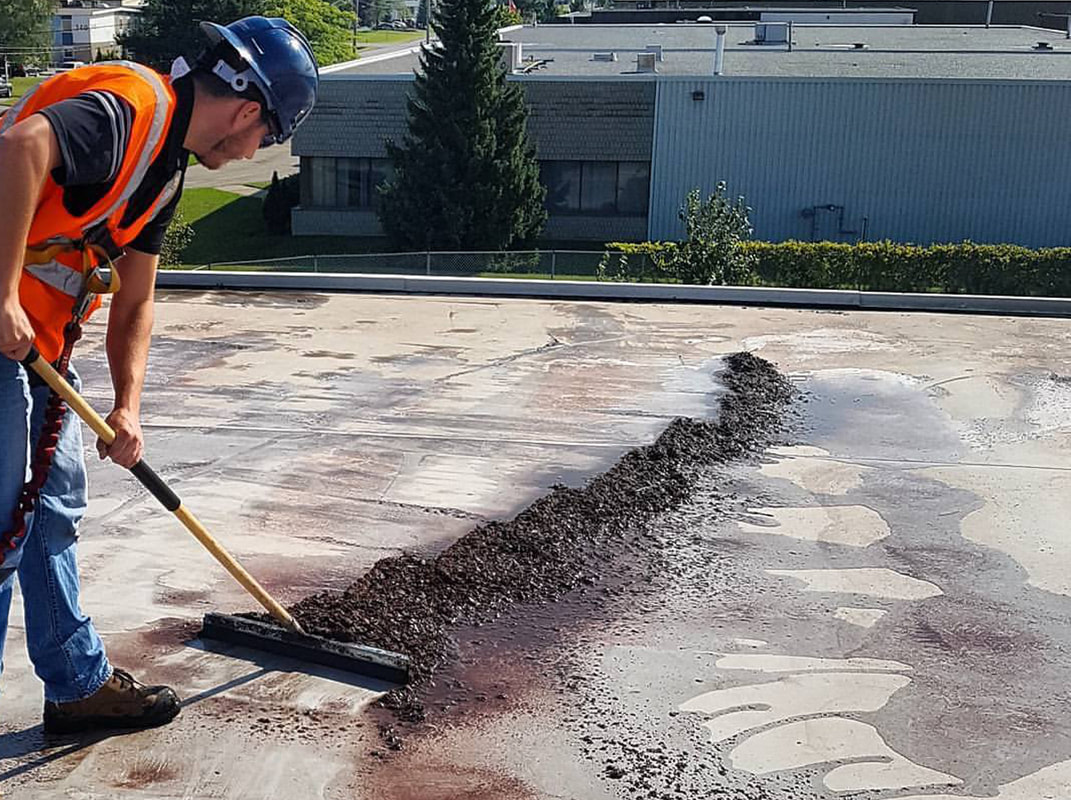 Photo of an alliance roofing employee cleaning a commercial flat roof